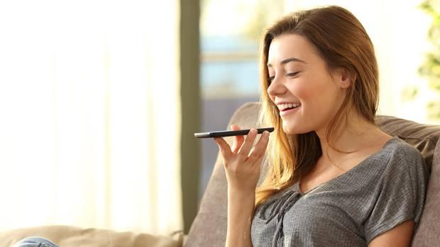 Eine Frau spricht in das Mikro ihres Smartphones