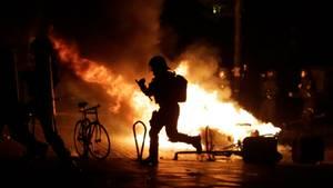 G20-Protest in Hamburg: Polizist als Schattenmann vor einem Feuer im Schanzenviertel