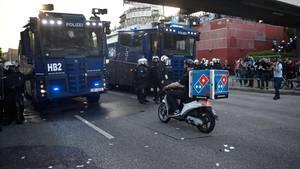 """Ein Held bei der Arbeit: Dieser Pizzabote bahnt sich seinen Weg durch die """"Welcome to Hell""""-Demo gewaltbereiter G20-Gegner"""