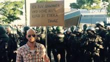 """Mit viel Humor gegen den G20-Gipfel: """"Ich bin so wütend, ich habe zum Einkaufen gehen ein Schild gemacht"""", schreibt der Comedian Andre Kramer auf Facebook und lässt sich vor einer Polizeikolonne fotografieren."""