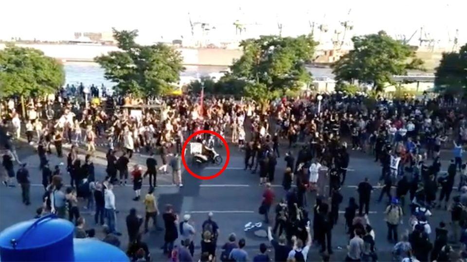 Ein Pizzabote fährt seine Lieferung auf dem Mofa mitten durch die Demonstranten