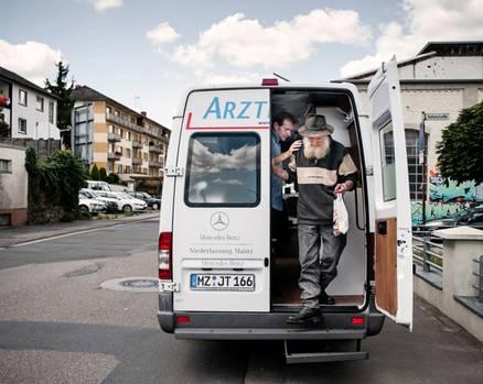 """Arztmobilsprechstunde in Bingen: """"Der Feind ist schon längst in uns selbst, wenn wir die Menschen vergessen"""", sagt Sozialmediziner Gerhard Trabert (links). Mit dem Arztmobil fährt er mehrmals in der Woche zu bedürftigen Menschen. Gehwege und öffentliche Plätze werden zu Sprechzimmern."""