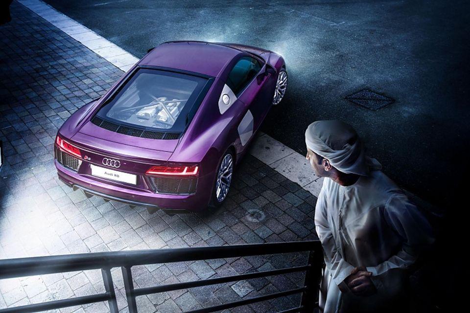 Am Ende glänzt sein Sportwagen in den Farben Lila, Grau im Scheinwerferlicht.