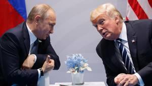 Russlands Präsident Wladimir Putin und US-Präsident Donald Trump beugen sich bei einem Gespräch zueinander
