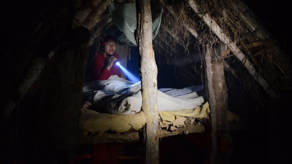 Ein einer winzigen Holzhütte mit Strohdach hockt eine Nepalesin und liest im Schein einer Taschenlampe