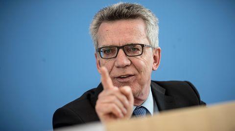 Vor blauem Hintergrund gestikuliert Bundesinnenminister Thomas de Maizière mit gestrecktem rechten Zeigefinger