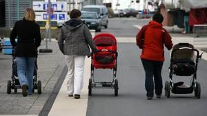 Streit um einen Kinderwagenstellplatz eskaliert. Drei Mütter laufen mit ihren Kinderwagen eine Straße entlang. (Symbolbild)