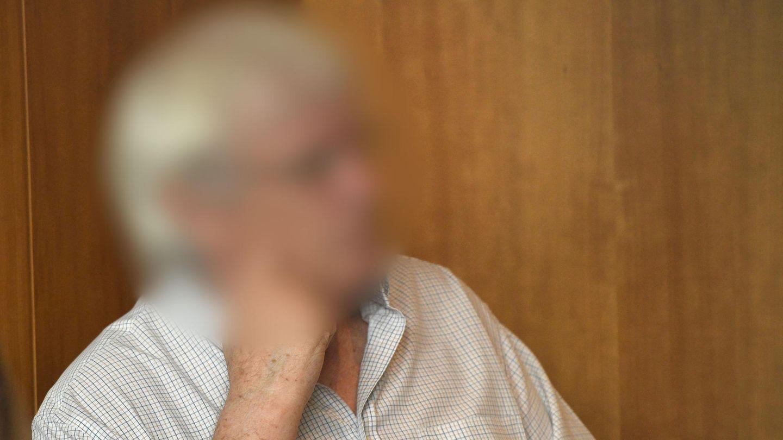 Ein weißhaariger Mann mit Brille sitzt vor einer hellbraunen Holzwand in einem Saal des Landgerichts Bonn