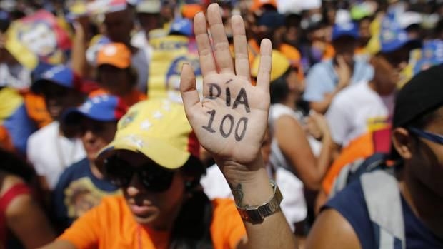 """Venezuela: Eine Demonstrantin hebt ihre Hand, auf der """"Tag 100"""" steht"""