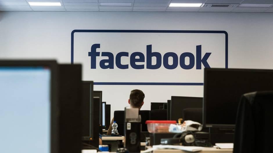 """Mitarbeiter sitzen im Löschzentrum von Facebook in einem Service-Center in Berlin an Computern. An der Stirnseite des Großraumbüros steht der Schriftzug """"Facebook"""". An dem von der Bertelsmann-Dienstleistungstochter Arvato betriebenen Standort arbeiten 650 Menschen."""