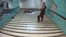 Fahndungsfoto der Polizei Berlin: Der Tatverdächtige steht am oberen Ende der U-Bahn-Treppe, während ein Mann herunter fällt.
