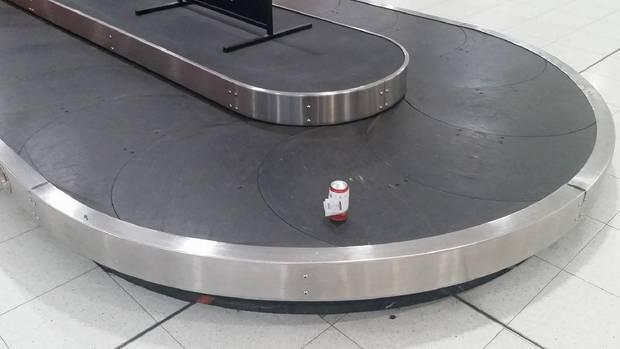 Eine Bierdose mit Gepäckaufkleber fährt auf einem Gepäckband am Flughafen