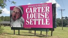 "Werbeschild mit Baby und Aufschrift ""Welcome to the World, Carter Louise Settle"""