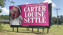 """Werbeschild mit Baby und Aufschrift """"Welcome to the World, Carter Louise Settle"""""""