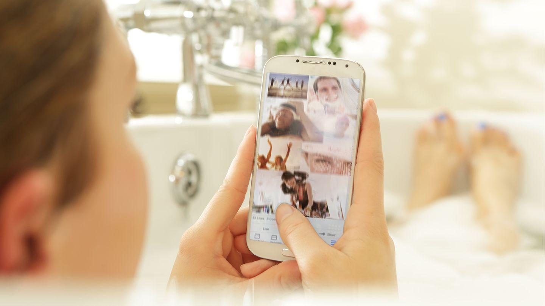 Eine junge Frau liegt mit ihrem Smartphone in der Badewanne (Symbolbild)