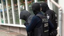 Polizisten führen in Berlin einen Mann (l.) in Zusammenhang mit dem Raub einer 100 Kilo schweren Goldmünze ab