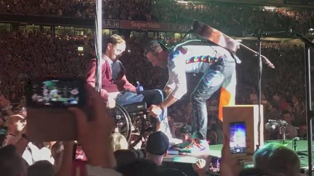 Coldplay-Sänger Chris Martin mit einem Fan im Rollstuhl