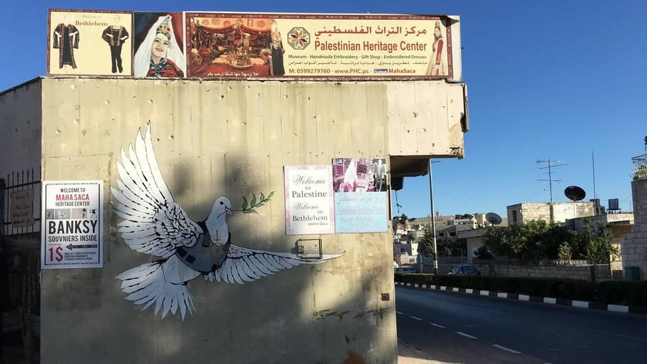 Eine weiße Friedenstaube mit kugelsicherer Weste und Zweig im Schnabel ist als Grafito auf einer Hauswand zu sehen