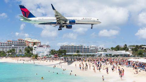 Auf Sint Maarten fliegt ein Flugzeug dicht über die Badegäste hinweg auf die Landebahn des Fluhafens zu