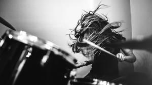 Mädchen spielt Schlagzeug mit fliegendem Haar