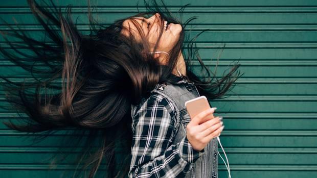 Eine Frau hört mit dem iPhone und den typischen, weißen Kopfhörern Musik