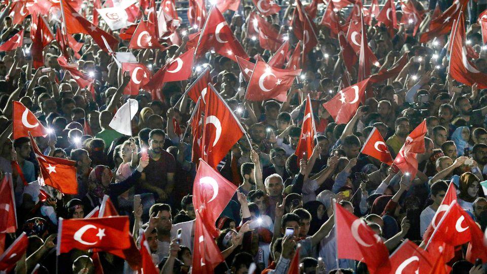 Teilnehmer einer Gedenkveranstaltung für die Opfer des gescheiterten Putschversuchs vor einem Jahr schwenken vor dem türkischen Parlamentsgebäude in Ankara Fahnen.