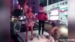 Chinesinnen feiern auf einem Polizeiauto
