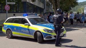 Ein Polizist steht mit Waffe und Dienstwagen vor der Friedrich-Ebert-Schule in Esslingen, Baden-Württemberg