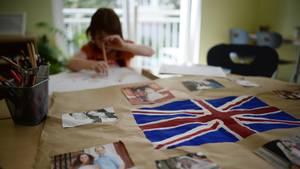 Ein kleines Mädchen sitzt am Tisch und malt. Vor ihr liegt die britische Flagge