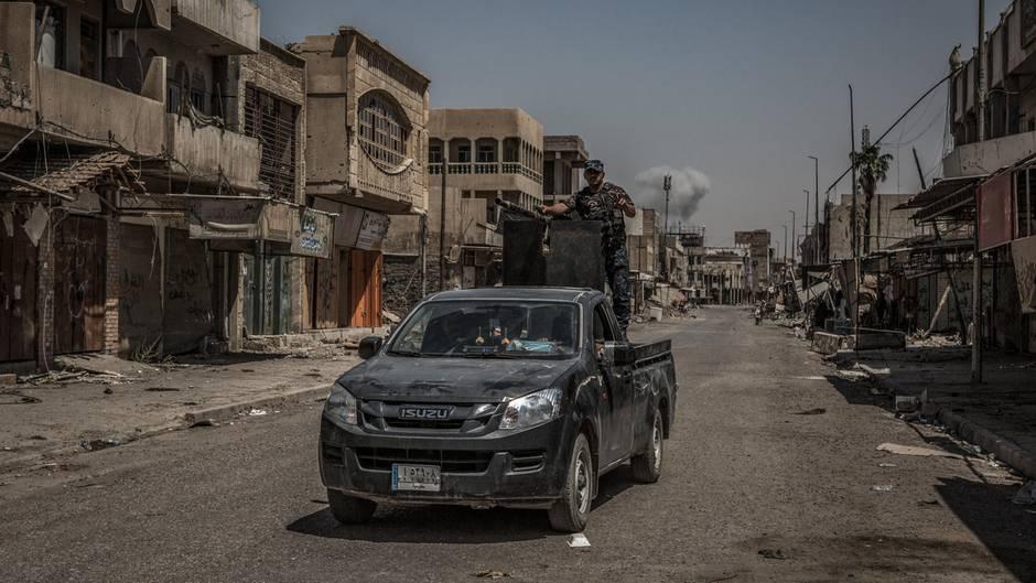 Eine Rauchsäule steigt in Mossul (Irak) hinter einen Polizeifahrzeug auf