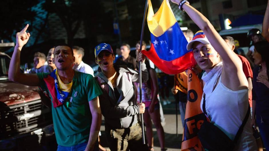 Menschen in Caracas in Venezuela auf den Straßen und protestieren mit Flaggen gegen Präsident Maduro