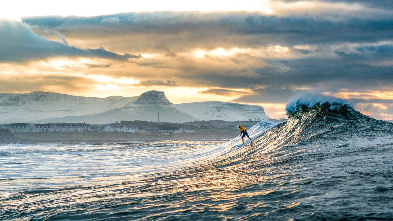 """""""Der Surfer Nic von Rupp surft eine winterliche Welle vor den schneebedeckten Bergen bei Bundoran, Irland."""""""