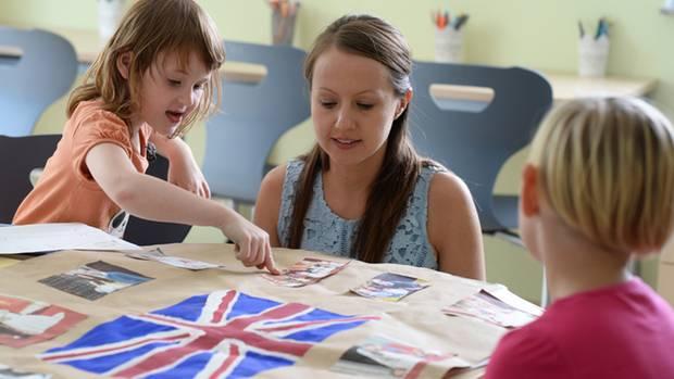 """Zwei Kinder bei """"Straßenkinder e.V."""" in Berlin Marzahn bereiten sich mit einer Betreuerin auf den Besuch der britischen Royals vor."""