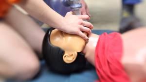 Ein Rettungssanitäter führt an einer Puppe eine Herz-Lungen-Massage durch