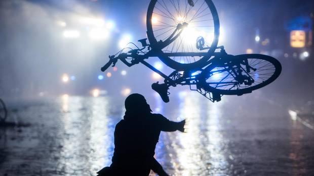 Ein Randalierer wirft in Hamburg im Schanzenviertel ein Fahrrad in Richtung von Wasserwerfern