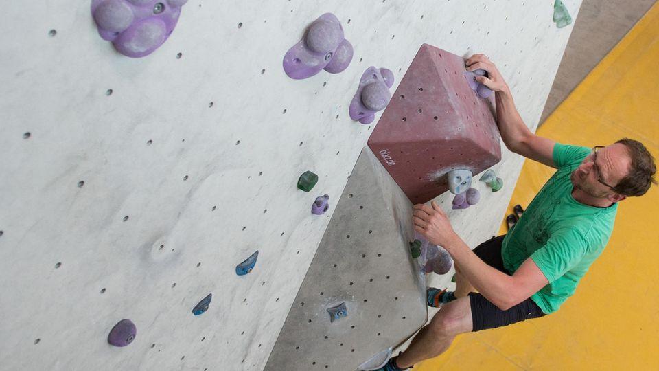 Ein Teilnehmer einer Studie, die Bouldern gegen Depressionen erforscht, an der Kletterwand