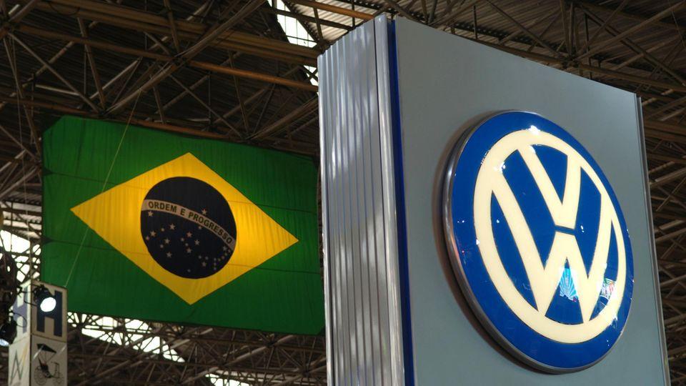 Das Volkswagen Symbol und die brasilianische Flagge in einem Werk in Sao Paulo