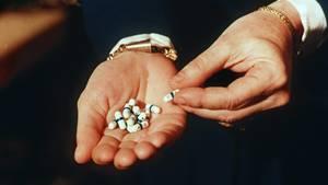 Zu sehen ist eine offene Handfläche, in der einige Tabletten liegen. Hier das HIV-Medeikament Retrovir.