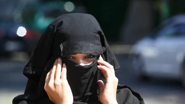 Eine junge Frau, die einen Nikab trägt, blickt in die Kamera.