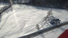 Luftaufnahme von Reifenspuren in Form eines Mittelfingers im Schnee