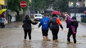 Sommer 2017: Eine Gruppe Menschen watet durch nach Dauerregen überflutete Straßen in Bad Harzburg