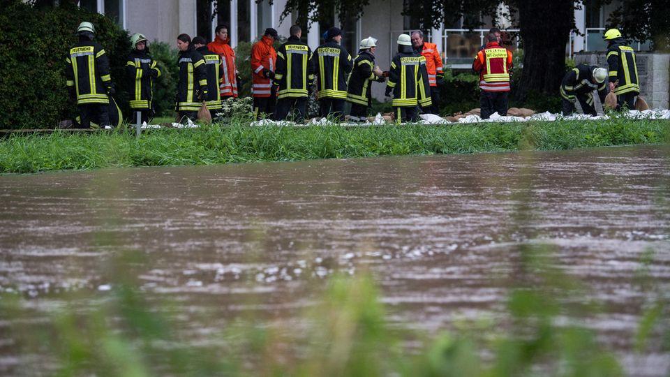 Regen ebbt ab, doch der Pegel der Innersten in Hildesheim steigt wieder an - Feuerwehrleute stabilisieren den Sandsäcke-Damm
