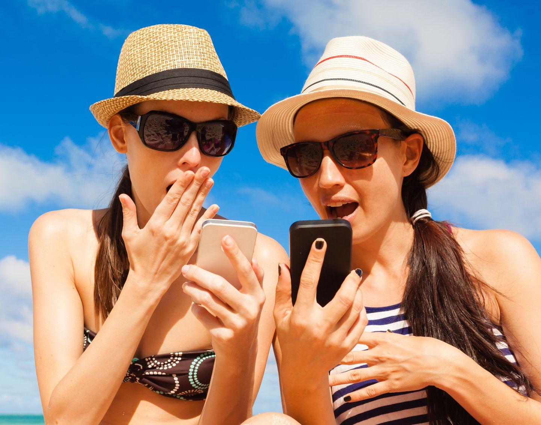 O2-Drosselung: Zwei Frauen in Strand-Kleidung schauen geschockt auf ihr Smartphone