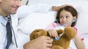 Mädchen liegt in Krankenhaus-Bett, der Doktor untersucht auch den Teddybären