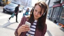 Eine junge Frau läuft über die Straße, während sie auf ihrem Handy schreibt
