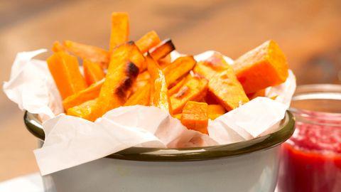 Süßkartoffel-Pommes in einer Schale. Daneben steht ein Glas mit Ketchup.