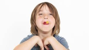 Ein Junge zeigt Weingummis auf seiner Zunge