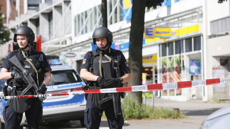 Einsatzkräfte der Polizei sperren nach einer Messerattacke in einem Supermarkt in Hamburg den Tatort ab