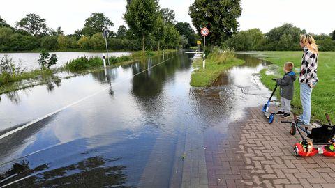 Eine Frau und ein Junge mit einem Roller stehen auf einem Fußweg. Beide schauen auf eine Landstraße, die überflutet ist