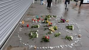 Blumen und Kerzen liegen am Samstag in ein Peace-Zeichen auf dem Bürgersteig vor dem Hamburger Supermarkt, in dem am Freitag ein Mann einen Menschen mit einem Messer getötet und sechs weitere verletzt hat.